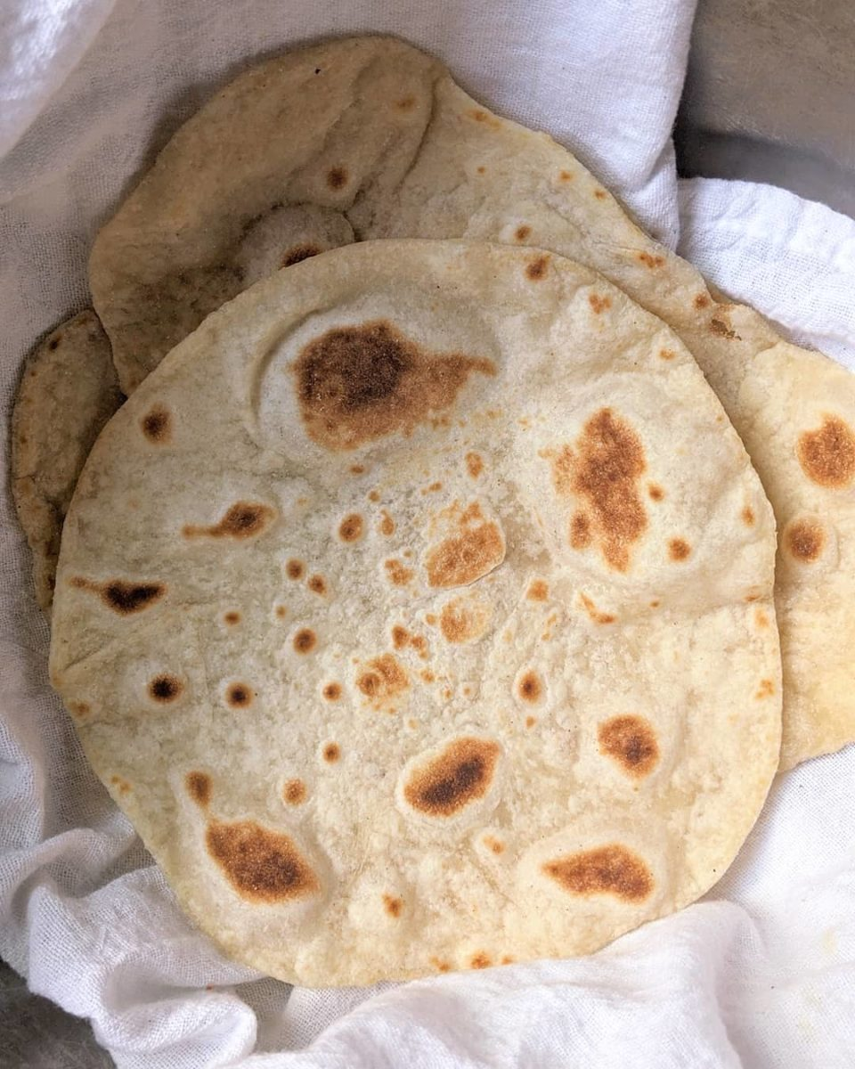 Warm homemade flour tortillas, piled into a white cloth.